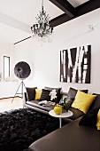 Dark grey leather corner couch on long-pile, black rug, chandelier and studio lamp in designer interior