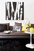 Dark grey leather couch with scatter cushions in various colours below black and white picture on wall; white orchid on white classic side table to one side