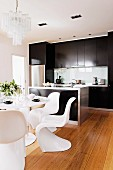 White designer shell chairs and table on wooden floor in front of modern counter and black fitted kitchen cupboards