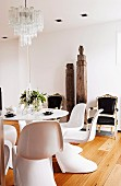 White designer shell chairs around Tulip Table, antique armchairs with black upholsters, Oriental wooden columns against wall in minimalist interior