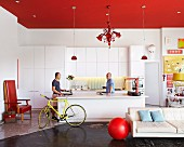 Open-plan interior with red ceiling above white kitchen area and men next to free-standing island counter; red ball next to white, designer sofa in foreground