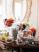 Selection of sweets, chocolates and pasties on antique table below mirror on wall