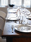 Wooden table set with white plates and glasses (detail)