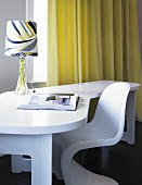 White desk, patterned lamp and designer chair