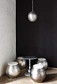 Barrel-shaped, metal stools, side table & pendant lamp in corner against black wall