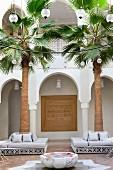 Marokkanischer Innenhof mit kreisförmiger Beleuchtung über Brunnen und Sitzgruppen um Palmen vor Arkaden
