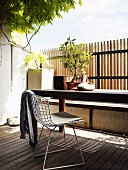 Bauhaus chair and table on sunny wooden deck with fence