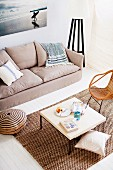 View down onto coffee table and sisal rug next to sofa against wall below large photograph