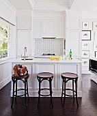 Thonet-Barhocker vor weißem Mittelblock in offenem Küchenbereich im Landhausstil