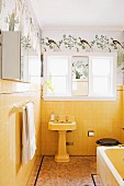 Vintage bathroom with pedestal sink against yellow wall tiles below stencilled frieze with bird motif