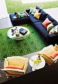View down into spacious seating area with round glass table, green rug, modern couch and yellow, Neo-Rococo armchairs