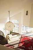 View down into living area with Oriental rug, modern, white chaise longue & spherical pendant lamp