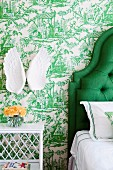 Bedside table next to partially visible bed with green, upholstered headboard; angel's-wings ornament on wall with toile de jouy wallpaper