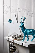 White wooden table with white wooden star, turquoise glittery reindeer, silver baubles and Christmas motto formed from wire in background