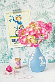 Pink hydrangea in vase next to spool of yarn on surface in front of vintage poster on blue and white wallpaper