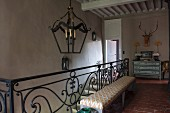 Wrought iron balustrade of staircase with bench and pendant lamp on landing