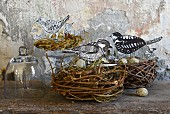 Hand-crafted paper birds and quail eggs in birds' nests on wooden surface against wall with peeling paint