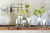 Craft idea - glass vessels dipped in white paint holding flowers on surface against weathered stone wall