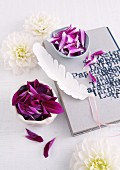 White dahlia flowers, china bowls of purple petals and white feather on diary with printed cover