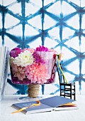 Glass bowl of dahlia flowers, black chair ornament and book in front of wall with blue mesh pattern
