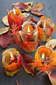 Windlicht mit Herbstlaub dekoriert