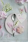 Herzförmiger Namensschild, Rosenblütenplätzchen und Löffel mit Maiglöckchen auf Teller