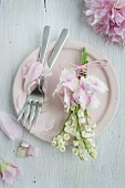 Posy of lily-of-the-valley and hydrangeas on pink plate scattered with peony petals