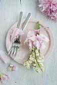 Sträusschen aus Maiglöckchen und Hortensien auf rosa Teller mit Pfingstrosenblütenblättern