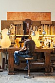 Violin-maker sitting in front of half-finished instruments on illuminated workbench