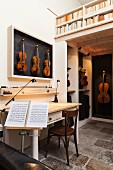 Living area in instrument-maker's workshop with vintage table, violins in display case, music stand and bookcase balustrade