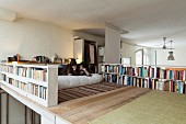 Young couple reading on wooden mezzanine surrounded by books on balustrade bookshelves