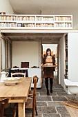 Junge Frau mit Tablett unter weiß gestrichener Holzgalerie in offenem Wohnraum mit Vintage-Flair und Stauraumlösung für Bücher