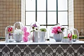 Flower arrangements in white china vases under glass covers on white lace tablecloth in front of industrial window