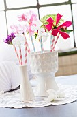 Summer flowers and drinking straws in two white china vases