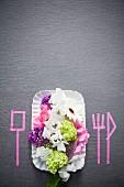 Gedeck mit Sommerblüten und mit Masking Tapes aufgeklebten Besteck-Silhouetten auf grauem Untergrund