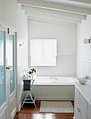 Elegant country-house-style, white bathroom with wood-clad bathtub and half-height wood panelling