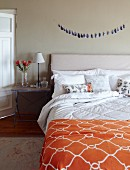 Double bed with headboard, orange bedspread with ogee pattern and rustic bedside table in simple bedroom