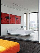 Red triptych above pedestal bed in loft apartment; view of Johannesburg cityscape through glass wall