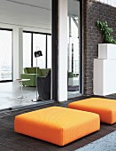 Orange ottomans on dark wooden terrace with view into living area of loft apartment through open sliding glass wall