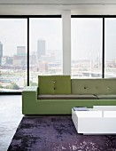 Polder sofa in shades of green and white coffee table in loft apartment with view of Johannesburg, South Africa