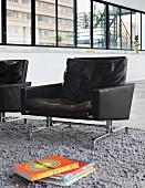 Black retro leather armchairs on grey, long-pile rug in designer loft apartment
