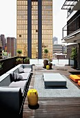 Spacious seating area with designer furniture on loft terrace; view of high-rise cityscape in Johannesburg, South Africa