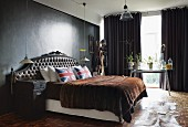 Double bed with antique headboard, Union Flag scatter cushions and fur blanket in bedroom with dark-painted walls and dark grey curtains