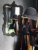 Hat and boxing gloves hanging on coat stand in front of mirror with ornate metal frame on grey-painted wall