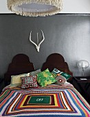 Colourful, crocheted blanket and scatter cushions on double bed with curved wooden headboards below hunting trophy on grey-painted wall