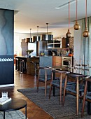 Open-plan interior - 60s-style chairs, spherical wooden pendant lamps and counter below pendant lamps with metal shades in kitchen area in background