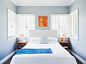 Simple double bed below retro-style portrait and ornate windows in narrow bedroom with pale grey walls