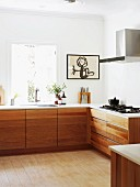 Modern L-shaped kitchen counter with solid wooden base units and framed child's drawing on wall next to window