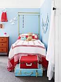 Vintage Kofferstapel in hellblau und rot vor Kinderbett mit Baldachingestell in hellblau getöntem Mädchen-Kinderzimmer