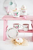 Floral-patterned cups and Easter decorations on pink footstool